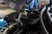 istock Car mechanic fills a fresh lubricant engine oil 1050618982