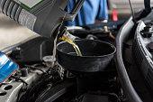 istock Car mechanic fills a fresh lubricant engine oil 1057452904