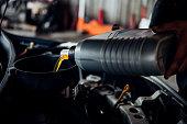 istock Car mechanic fills a fresh lubricant engine oil 1186673526