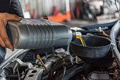 istock Car mechanic fills a fresh lubricant engine oil 1186673644