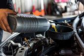 istock Car mechanic fills a fresh lubricant engine oil 1194657386
