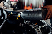 istock Car mechanic fills a fresh lubricant engine oil 1196924093