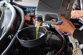 istock Car mechanic fills a fresh lubricant engine oil 1196924144