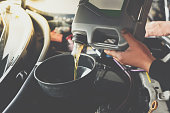 istock Car mechanic fills a fresh lubricant engine oil 1202005478