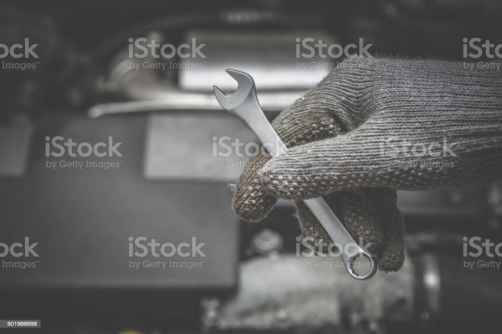 Car mechanic hand in protective glove holding a wrench in the garage....
