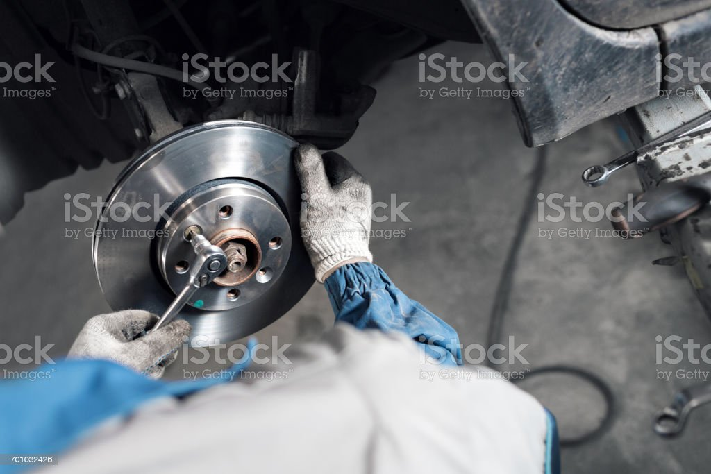 Car mechanic hands replace brakes in garage. stock photo