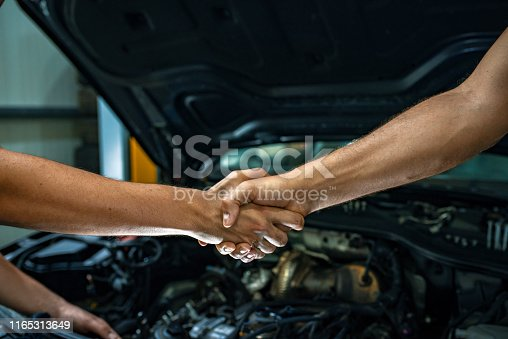 Caucasian young mechanic shaking hands with a mature male customer in front of a car. Photo of a  man giving an handshake in an industrial facility. Man greets auto master. Concept - car service. Handshake.