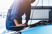 istock Car mechanic holding clipboard and checking to maintenance vehicle by customer claim order in auto repair shop garage. Engine repair service. People occupation and business job. Automobile technician 1202418366