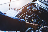 istock Car mechanic holding clipboard and checking to maintenance vehicle by customer claim order in auto repair shop garage. Engine repair service. People occupation and business job. Automobile technician 1202418370