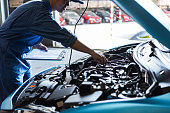 istock Car mechanic holding clipboard and checking to maintenance vehicle by customer claim order in auto repair shop garage. Engine repair service. People occupation and business job. Automobile technician 1202418372