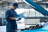 istock Car mechanic holding clipboard and checking to maintenance vehicle by customer claim order in auto repair shop garage. Engine repair service. People occupation and business job. Automobile technician 1202418375