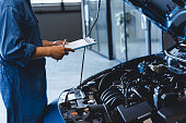 istock Car mechanic holding clipboard and checking to maintenance vehicle by customer claim order in auto repair shop garage. Engine repair service. People occupation and business job. Automobile technician 1202418376