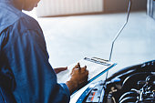 istock Car mechanic holding clipboard and checking to maintenance vehicle by customer claim order in auto repair shop garage. Engine repair service. People occupation and business job. Automobile technician 1202418393