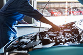 istock Car mechanic holding clipboard and checking to maintenance vehicle by customer claim order in auto repair shop garage. Engine repair service. People occupation and business job. Automobile technician 1219905269
