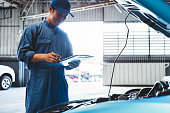istock Car mechanic holding clipboard and checking to maintenance vehicle by customer claim order in auto repair shop garage. Engine repair service. People occupation and business job. Automobile technician 1222187918