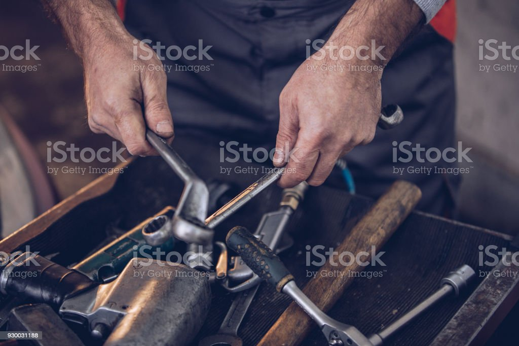 One man, mature adult auto mechanic holding work tools in auto repair...