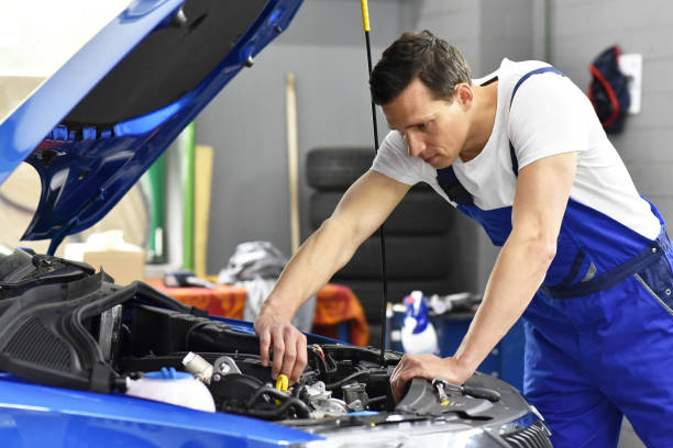 car mechanic in a workshop repairing a vehicle stock photo
