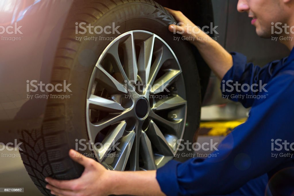 Car mechanic in workshop changing tires stock photo