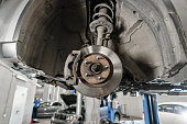 istock Car mechanic inspecting car wheel and repair suspension detail. Lifted automobile at repair service station. replacement of ferrule and leverage 1022676226