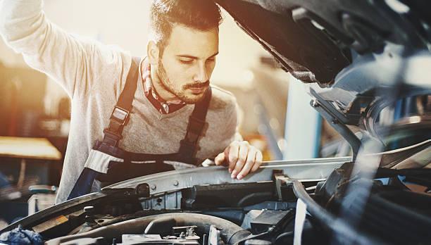 Car mechanic inspecting engine during service procedure. – zdjęcie