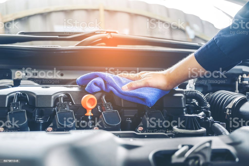 Car mechanic inspecting engine during service procedure stock photo