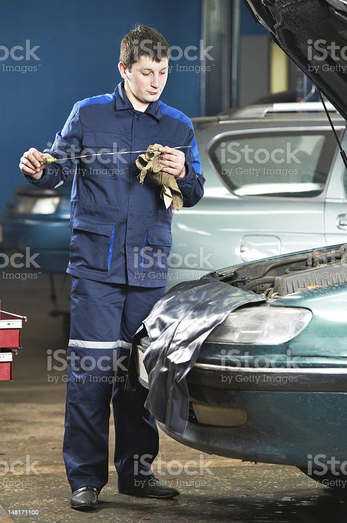 car mechanic inspecting engine oil level royalty-free stock photo