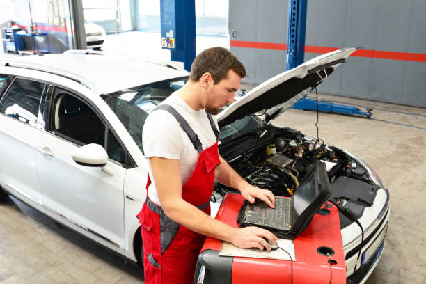 car mechanic inspects vehicle in a workshop - electronic computer check up stock photo