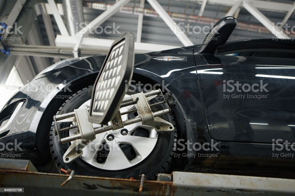 car mechanic installing sensor during suspension adjustment and automobile wheel alignment work at repair service station stock photo