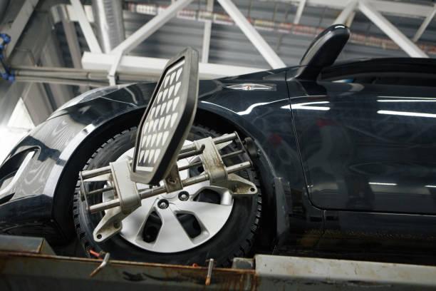 capteur installation mécanique de voiture pendant le réglage de la suspension et l'alignement de roue automobile travaillent à la station de service de réparation - convexe photos et images de collection