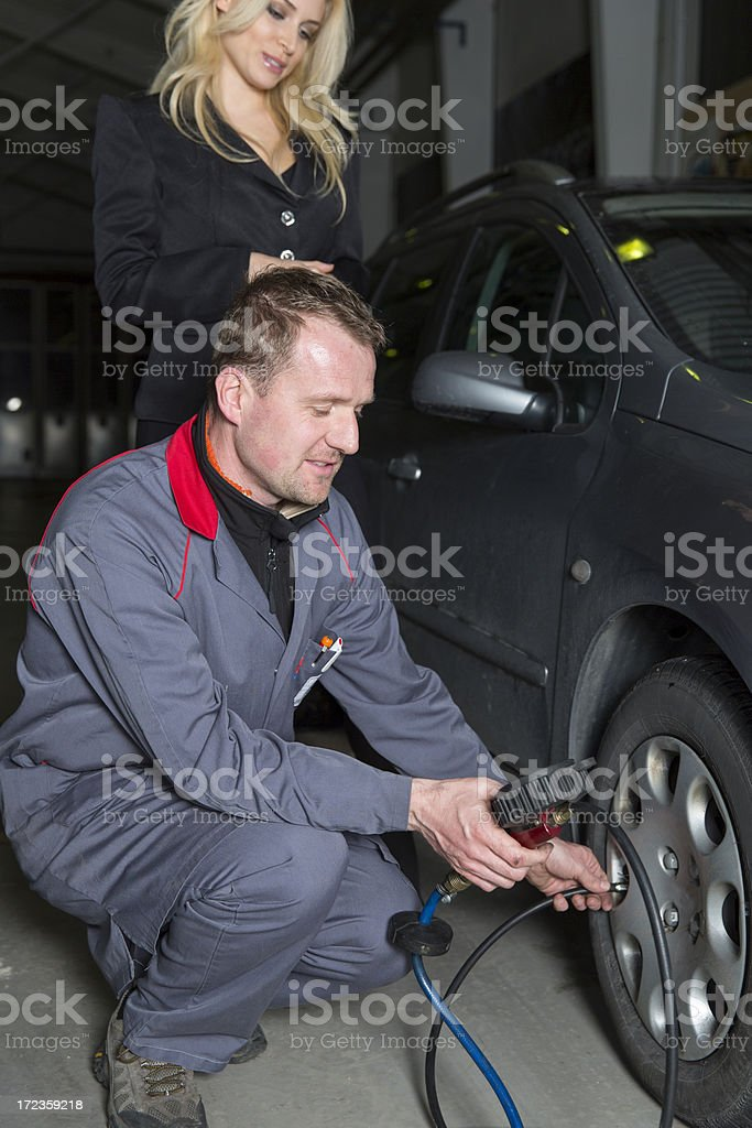 Car mechanic is checking tire pressure....cute customer observing him royalty-free stock photo