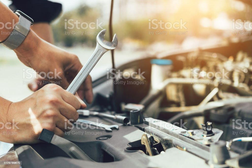 Car mechanic is holding a wrench ready to check the engine and maintenance. Car mechanic is holding a wrench ready to check the engine and maintenance. Adjusting Stock Photo