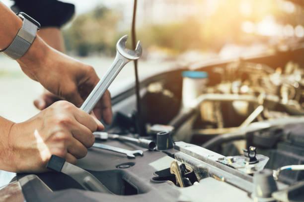 kfz-mechaniker hält einen schraubenschlüssel bereit, den motor und die wartung zu überprüfen. - autowerkstatt stock-fotos und bilder
