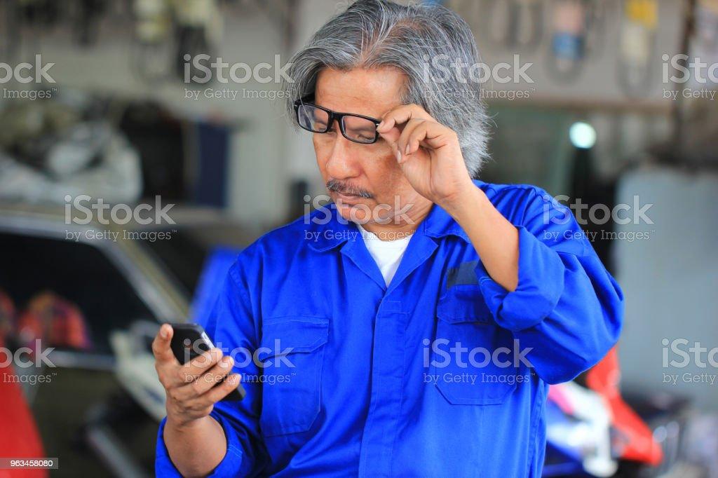 Araba tamircisi smartphone oto tamir servisi olarak bakıyor. - Royalty-free Araba - Motorlu Taşıt Stok görsel