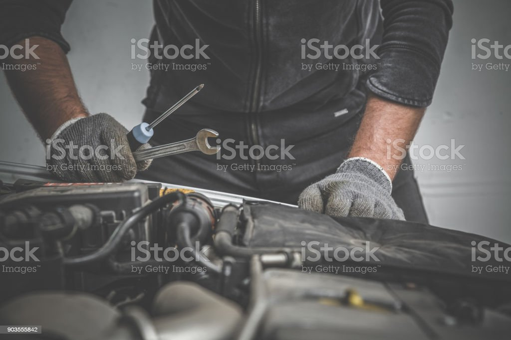 Car mechanic looking to the engine in the garage. Car motor repair. Problems and solutions concept. stock photo