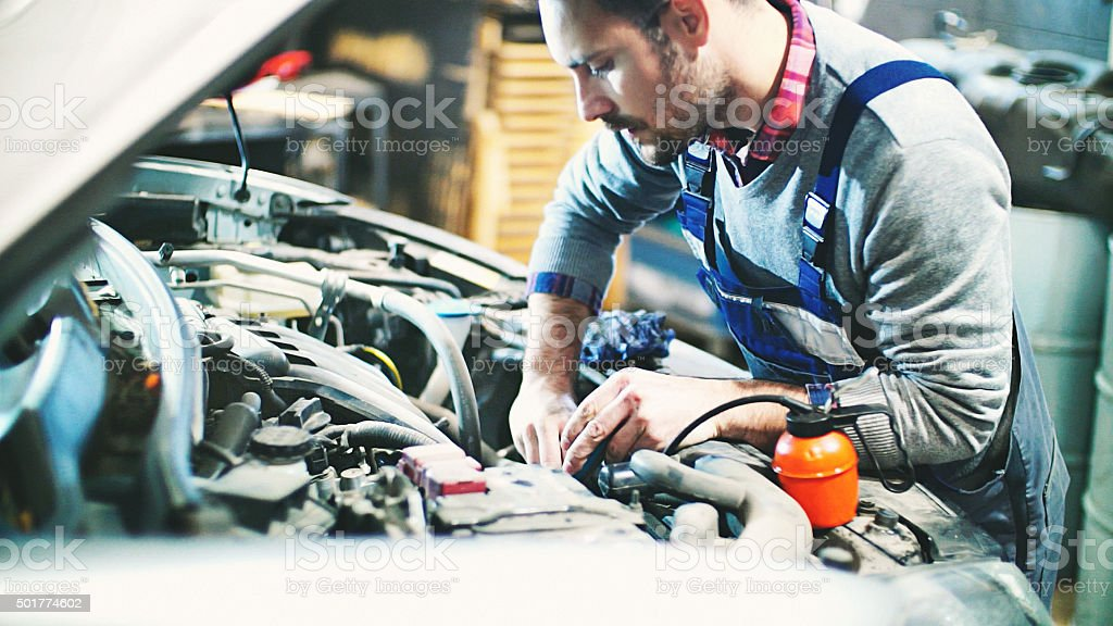 Car mechanic repair an engine. stock photo