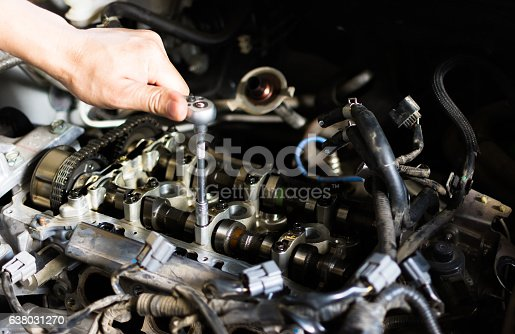 1073743202 istock photo Car mechanic repairing an internal combustion engine. 638031270