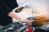 istock Car mechanic repairing vehicle engine working job. 1129789673