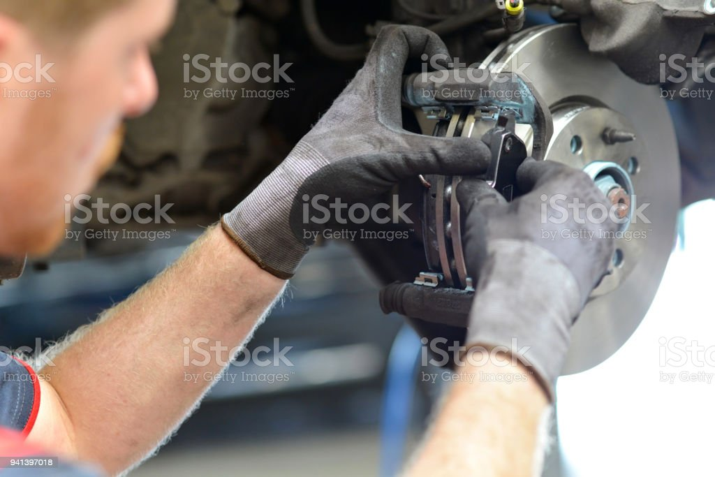 car mechanic repairs breakes from vehicle in a workshop stock photo