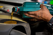 istock Car mechanic replacing and pouring fresh oil into engine at maintenance repair service station, Mechanic pouring oil into car at the repair garage. Fresh oil being poured during an oil change to a car 1255250592