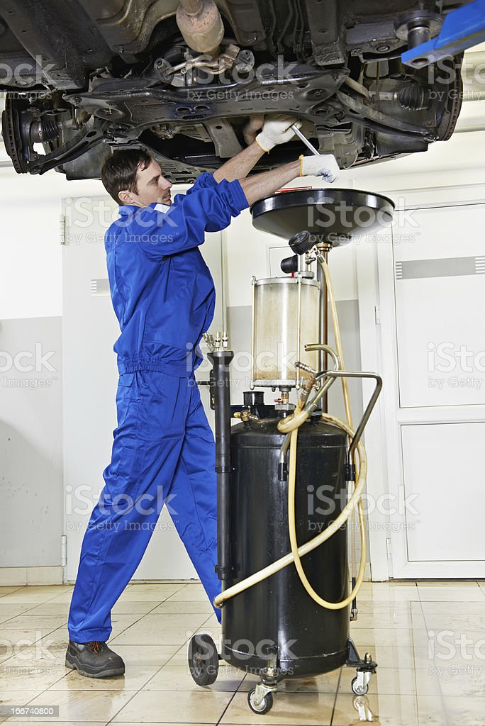 car mechanic replacing oil from motor engine royalty-free stock photo