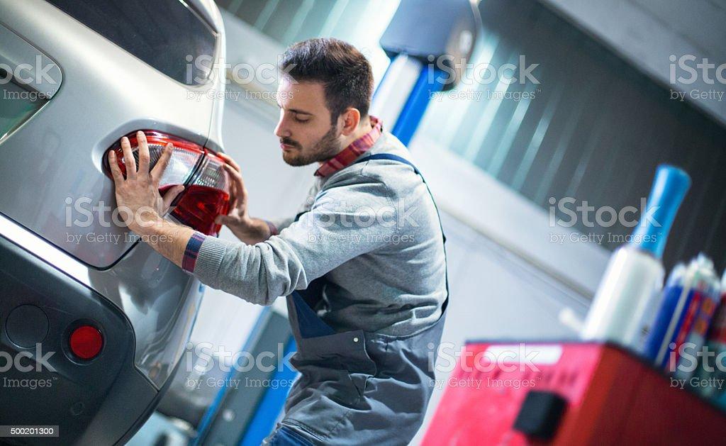 Auto Mechaniker ersetzt Rücklicht auf ein Fahrzeug. – Foto