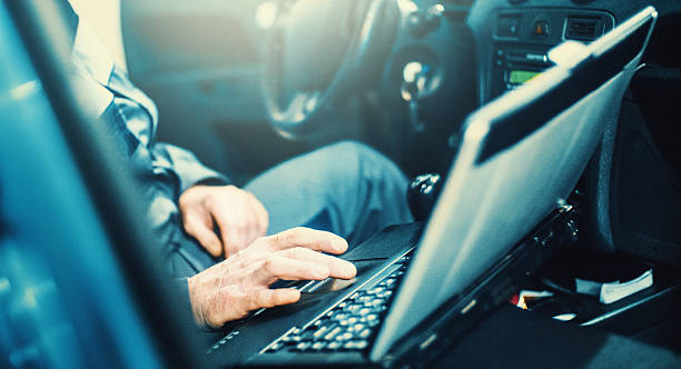 Car mechanic running diagnostics with laptop and OBD software. stock photo