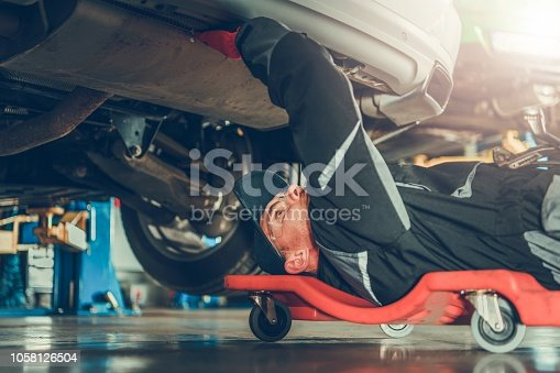 Caucasian Car Mechanic in His 30s Under the Car on the Mechanics Creeper Trying To Fix Modern Vehicle Exhaust System.
