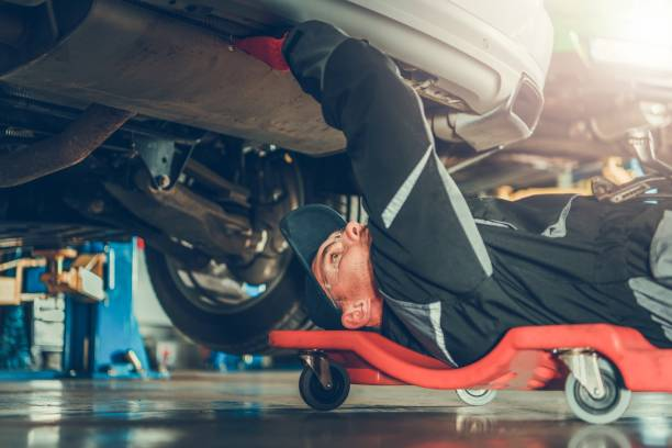 Car Mechanic Under the Car Caucasian Car Mechanic in His 30s Under the Car on the Mechanics Creeper Trying To Fix Modern Vehicle Exhaust System. mechanic stock pictures, royalty-free photos & images