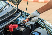 istock Car mechanic uses battery jumper cables to charge dead batte 514850872