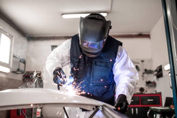 Automechaniker mit einem Lichtbogenschweißer, um ein beschädigtes Autoteil in einer Karosseriewerkstatt zu reparieren – Foto