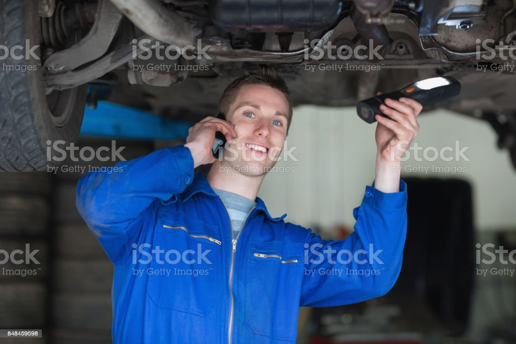 Car Mechanic using cell phone stock photo
