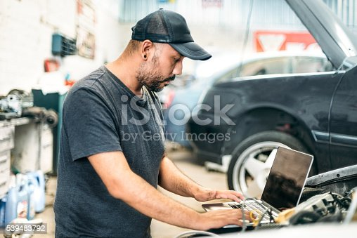 Car mechanic using computer diagnostics to identify issues the vehicle is having.
