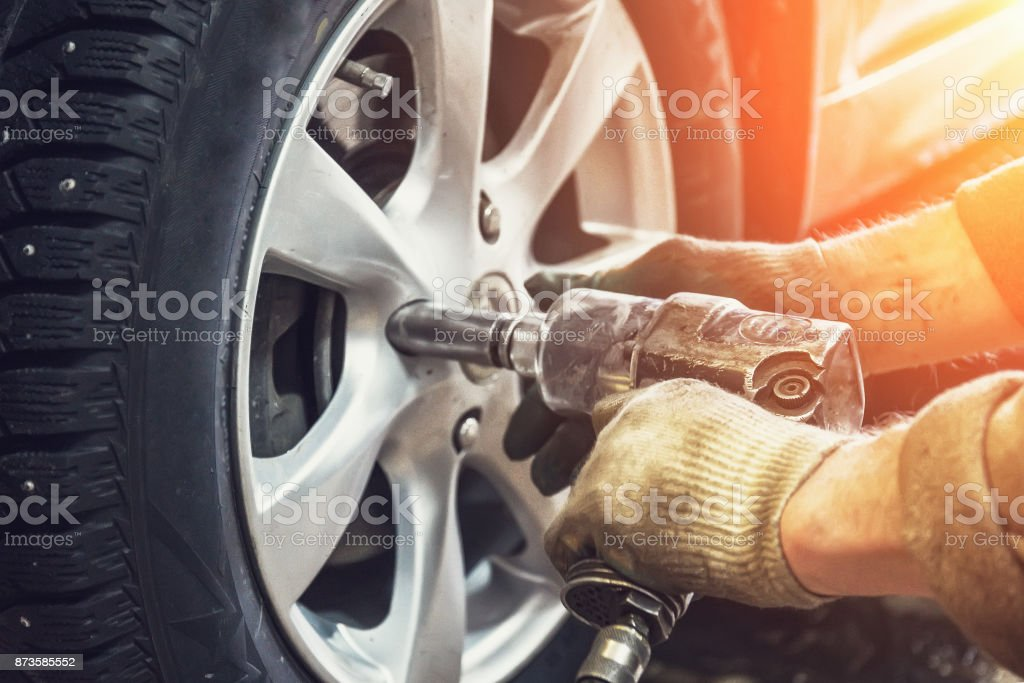 Car mechanic worker doing tire or wheel replacement with pneumatic wrench in garage of repair service station stock photo