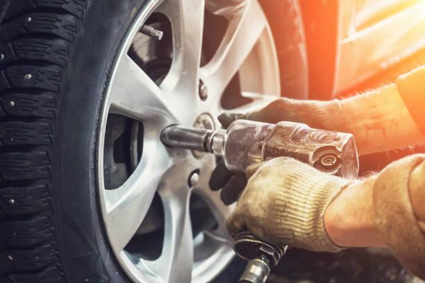 monteur werknemer uit de automobielsector doen van banden of wielen vervanging met pneumatische moersleutel in de garage voor reparatie service station - tyre stockfoto's en -beelden